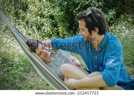 lovers couple in romance ourdoor on the hammock - stock photo