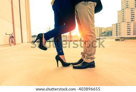 Lovers couple on date kissing and hugging on urban background at sunrise - Man and woman legs closeup outdoor - Concept of a romantic love story with vintage nostalgic filter look and warm tone - stock photo