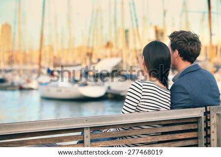 Lovers couple Romantic dating sitting on bench on date in old harbour, Port Vell, Barcelona, Catalonia, Spain. Happy woman and man embracing enjoying life and romance outside - stock photo