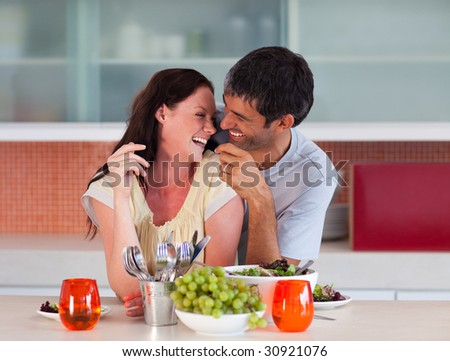 Lovers eating fruit in the kitchen - stock photo