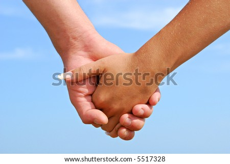 Lovers  holding each other from hands on the sky background - stock photo