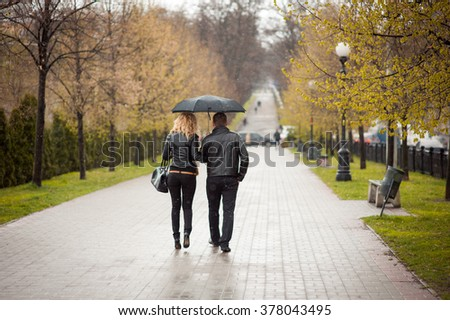 lovers holding hands and strolling through the park in the rain under an umbrella
