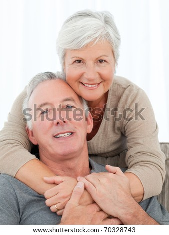 Lovers hugging while they are looking at the camera - stock photo