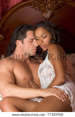 Lovers - Interracial sensual couple making love in bed - stock photo