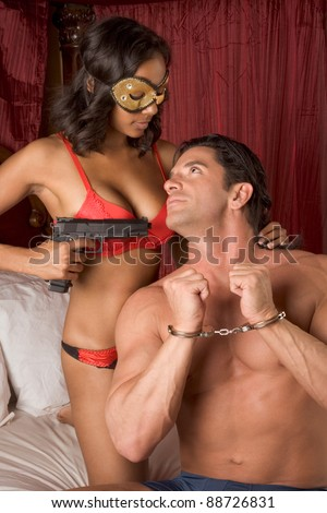 Lovers - Interracial sensual couple making love in bed. mystery love Woman in mask holding gun - stock photo