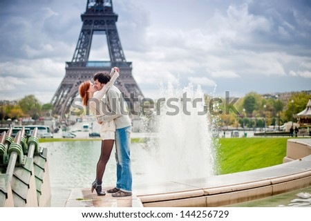 Lovers kissing in Paris with the Eiffel Tower in the Background - stock photo