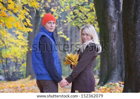 Lovers male and female walking in the autumn park - stock photo