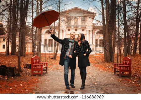 Lovers man and woman under an umbrella in the autumn forest - stock photo