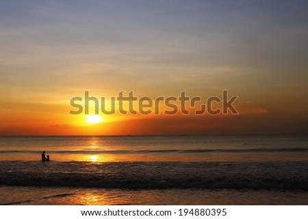 lovers on the ocean beach at sunset on Bali island, Indonesia, Jimbaran  - stock photo