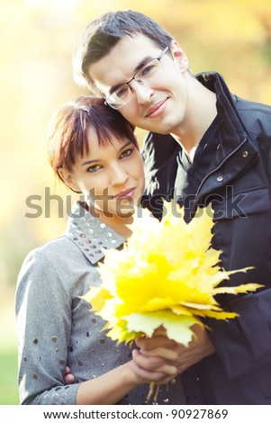 Lovers spend sunny day in the autumn park, they hold autumn leaves - stock photo