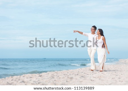 Lovers walking by the sea - stock photo