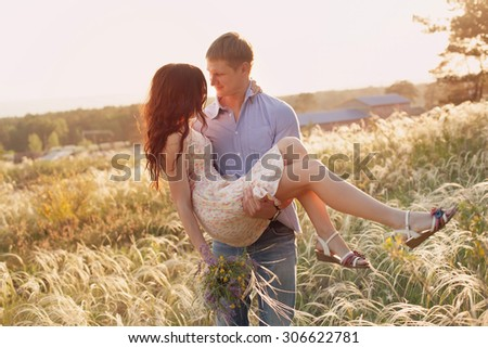 lovers walking in a field at sunset - stock photo