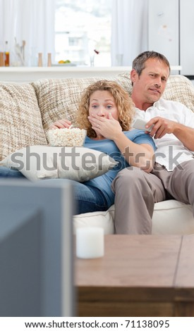 Lovers watching tv in the living room at home