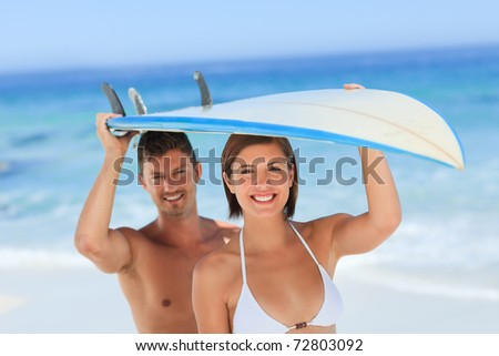 Lovers with their surfboard - stock photo