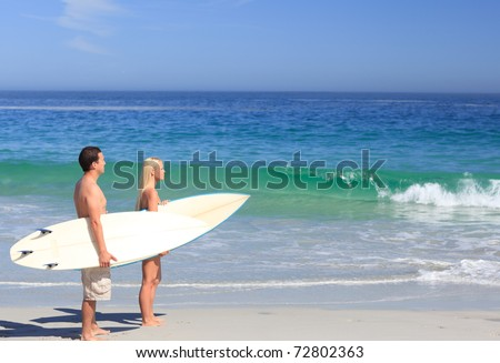 Lovers with their surfboards - stock photo