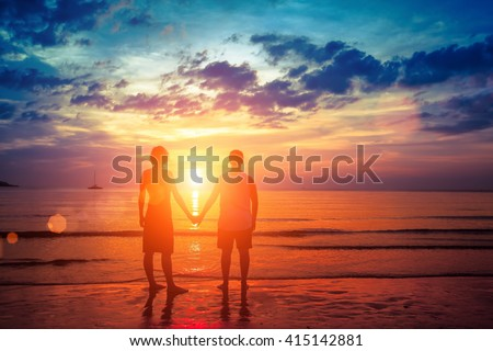 Lovers young couple standing hand in hand on the beach during sunset.