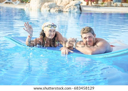 Loving adult couple bathing in the pool