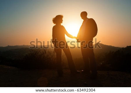 Loving adult couple together outdoor in mountains over scenic sunset sky background. - stock photo