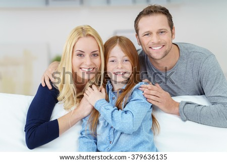 Loving affectionate happy young family with a pretty little redhead daughter posing arm in arm on a comfortable sofa at home smiling at the camera - stock photo