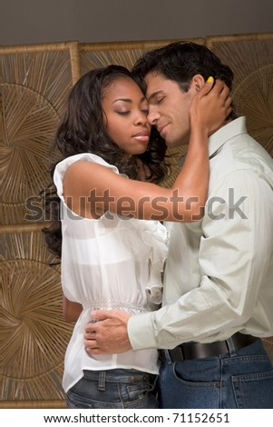 Loving affectionate heterosexual couple in affectionate sensual kiss. Mid adult Caucasian men in late 30s and young black African-American woman in 20s - stock photo