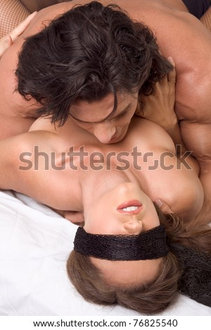 Loving affectionate heterosexual couple in affectionate sensual kiss. Woman eyes are covered by black scarf - stock photo