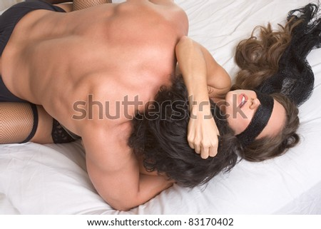 Loving affectionate heterosexual couple in affectionate sensual kiss. Woman eyes are covered by black scarf