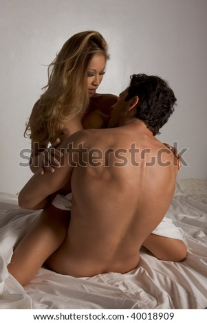 Loving affectionate nude heterosexual couple in bed engaging in sexual games. Mid adult Caucasian man and Asian Vietnamese woman - stock photo