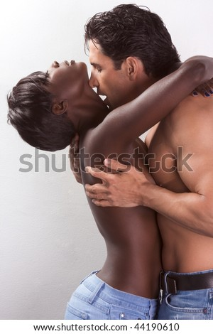 Loving affectionate nude heterosexual couple in sensual kiss and hug. Mid adult Caucasian men in late 30s and young black African-American woman in 20s - stock photo