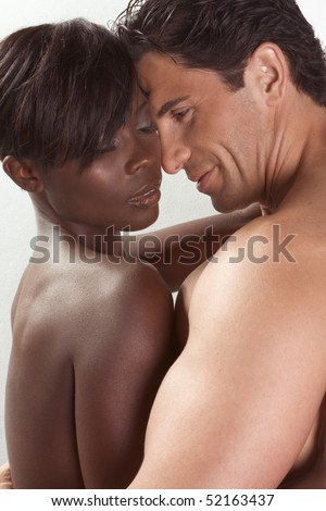Loving affectionate nude heterosexual couple in sensual kiss and hug. Mid adult Caucasian men in late 30s and young black African-American woman in 20s