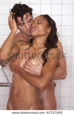 Loving affectionate nude heterosexual couple in shower engaging in sexual games, hugging and kissing. Mid adult Caucasian men in late 30s and young black African-American woman in 20s - stock photo