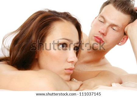 Loving affectionate nude heterosexual couple on bed - stock photo