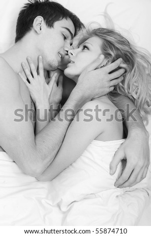 Loving affectionate nude heterosexual couple on bed.