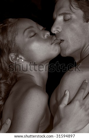 Loving affectionate nude interracial heterosexual couple in affectionate sensual kiss. Mid adult Caucasian men in late 30s and young black African-American woman in 20s - stock photo