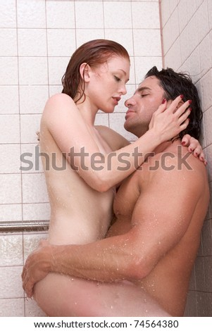 Loving affectionate nude young heterosexual couple in affectionate sensual kiss after taking shower. Mid adult Caucasian men in late 30s and young Caucasian redhead woman in early 20s - stock photo