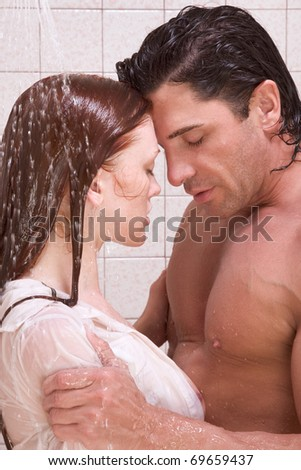 Loving affectionate young heterosexual couple in affectionate sensual kiss after taking shower. Mid adult Caucasian men in late 30s and young Caucasian redhead woman in early 20s - stock photo
