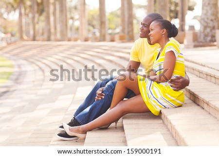 loving african american couple sitting together in park - stock photo