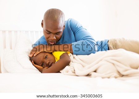 loving african father taking care of his ill son on bed - stock photo