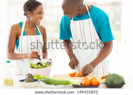 loving african husband and wife cooking dinner together - stock photo