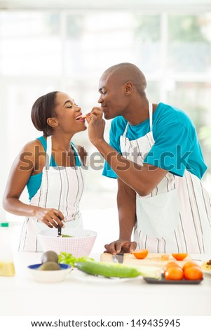 loving african husband feeding wife a piece of tomato while cooking - stock photo