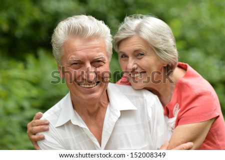 Loving aged couple on a background of trees - stock photo