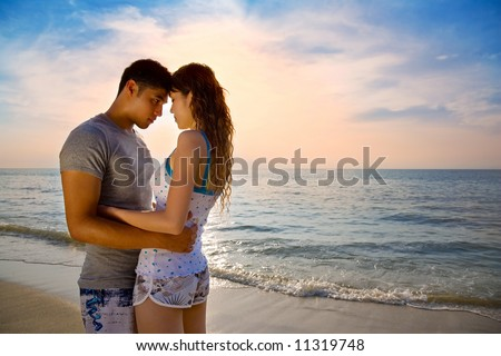 loving asian couple hugging each other on a beautiful romantic sunset beach