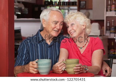 Loving attractive senior couple sitting at table in cafe - stock photo