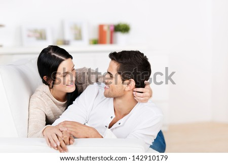 Loving attractive young couple cuddling on the sofa staring into each others eyes with tenderness - stock photo