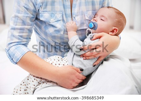 Loving baby with dummy sleeping in mother's hands, close up - stock photo