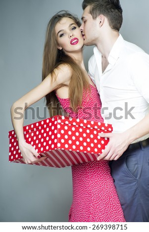 Loving beautiful couple standing close to each other, holding big spotted red present box, vertical photo - stock photo