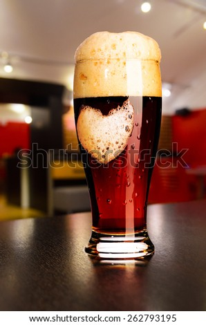 loving beer. glass of fresh draft dark beer on table in pub - stock photo
