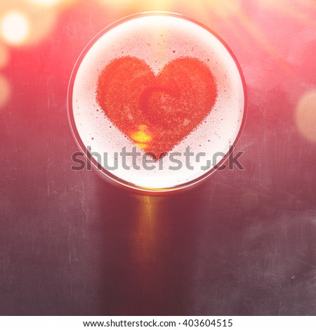 loving beer, heart symbol on foam in glass on black table, view from above - stock photo