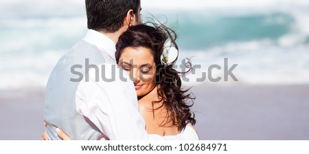 loving bride and groom hugging on beach