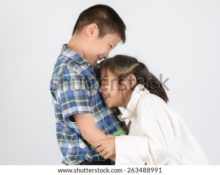 Loving brother and little sister hugging on gray background. - stock photo