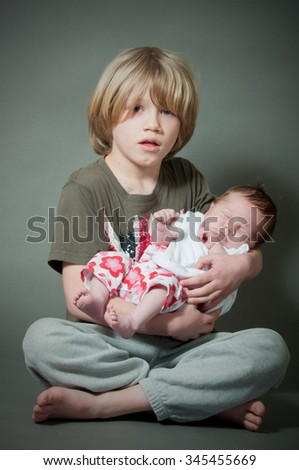 Loving brother holding his baby sister - stock photo
